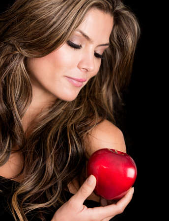 Beautiful woman holding the apple of tempation - isolated over black photo