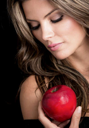 Beauty female portrait holding an apple - isolated over black background photo