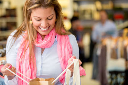 Happy woman looking into a shopping bag Stock Photo - 18572359