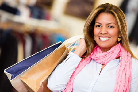Happy woman hodling shopping bags at the mall and smiling Stock Photo - 18572349