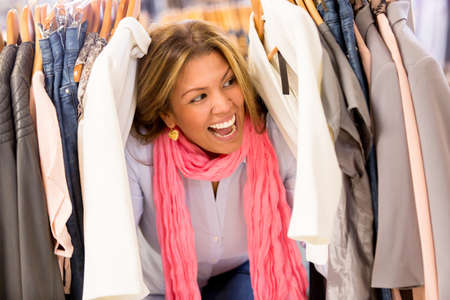 Excited woman shopping clothes on sale at retail store Stock Photo - 18572362