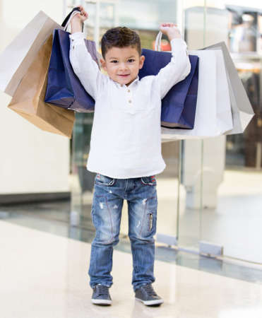 Happy boy holding shopping bags at the mall Stock Photo - 18572345