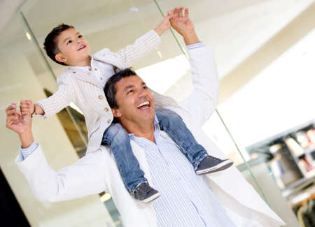 Father carrying son on his shoulders at the shopping center photo