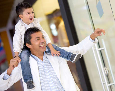 family latin: Father and son window shopping at the mall looking happy