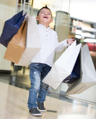 Happy shopping boy holding bags and smiling photo