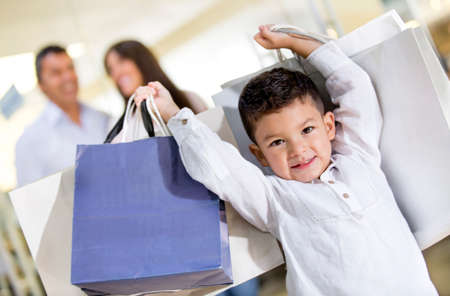 Happy little boy holding shopping bags with his family photo
