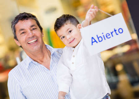 Dad carrying his son at the mall holding a Spanish open sign photo
