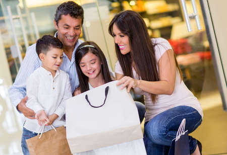 Happy family at the mall looking inside of a shopping bag photo