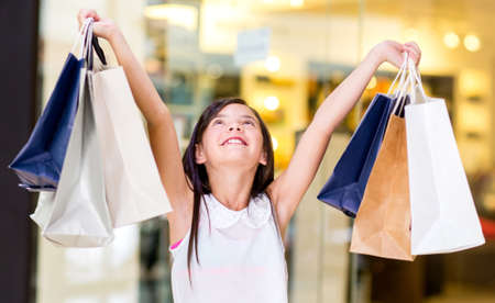 Happy girl holding shopping bags with her arms open photo