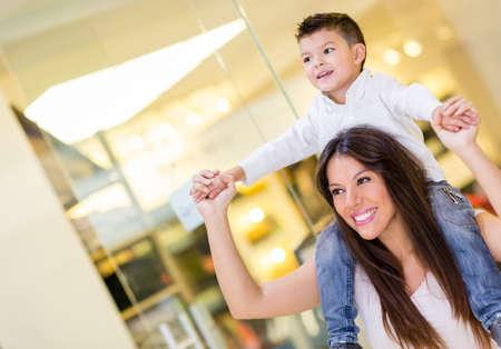 ni�os de compras: Mam� lleva a su hijo en sus hombros en el centro comercial