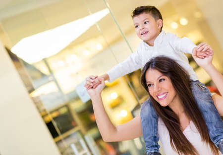 happy family shopping: Mom carrying her son in her shoulders at the mall Stock Photo