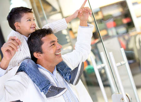 Father and son at the shopping center looking at a window photo