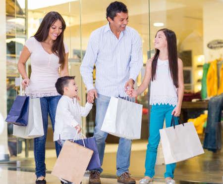 ni�os de compras: Familia de compras en el centro comercial y mirando muy feliz