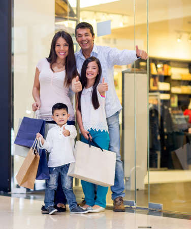 Happy family shopping with thumbs up and smiling photo