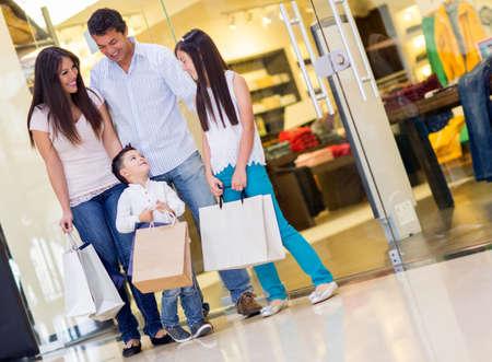 ni�os de compras: Familia feliz con bolsas de la compra en el centro comercial