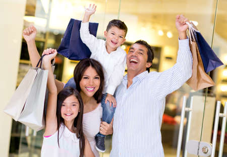 shoppers: Excited shopping family with arms up holding bags