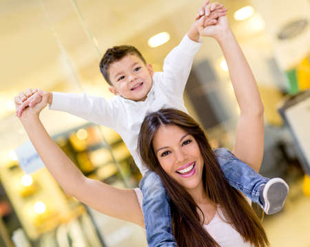 Mother carrying son on her shoulders at the shopping center photo