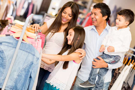 malls: Family shopping for clothes and looking happy Stock Photo
