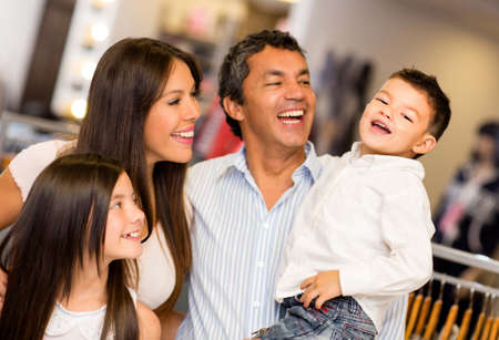 hispanic male: Shopping family looking very happy at a clothing store Stock Photo