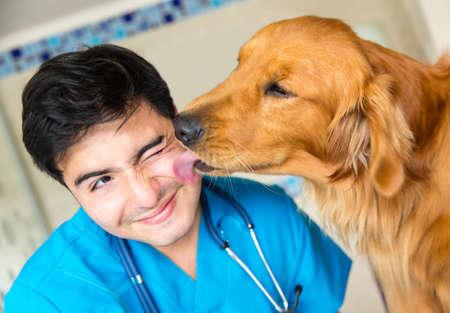 veterinario: Perro lindo que da un beso al veterinario despu�s de un examen Foto de archivo