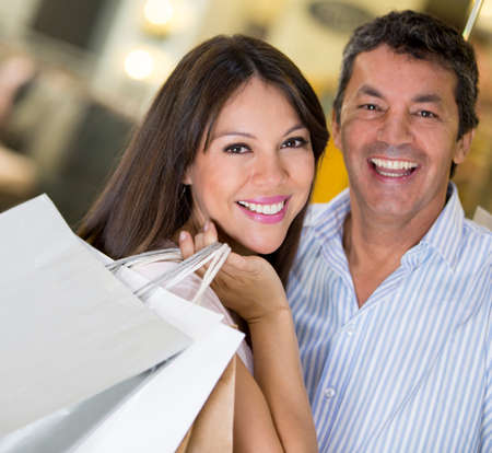 Happy couple shopping holding bags and smiling photo
