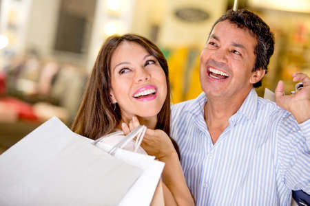 Happy couple at a shopping center holding bags photo