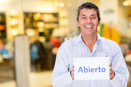 owner: Happy man at a retail store with an open sign smiling