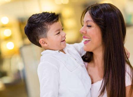 nios hispanos: Retrato de una madre feliz y su hijo en el centro comercial Foto de archivo