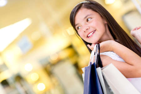 Beautiful thoughtful girl holding shopping bags and smiling photo