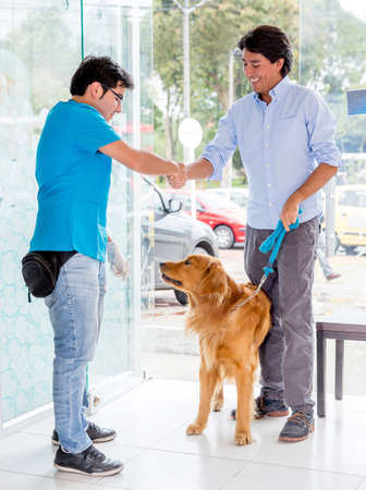 Man taking dog to the vet and handshaking the doctor photo