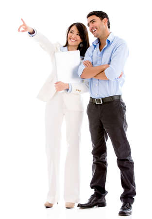 woman pointing: Successful business couple pointing away - isolated over white