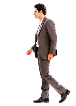 Business man walking to the side - isolated over a white background photo