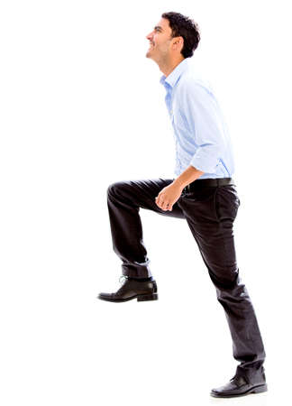stepping: Business man stepping up for success - isolated over a white background
