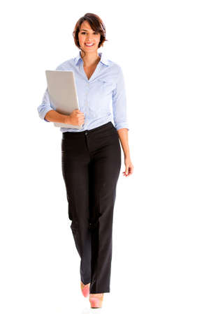 Business woman walking and carrying a laptop - isolated over white photo