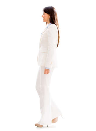 Business woman walking to the side - isolated over white photo