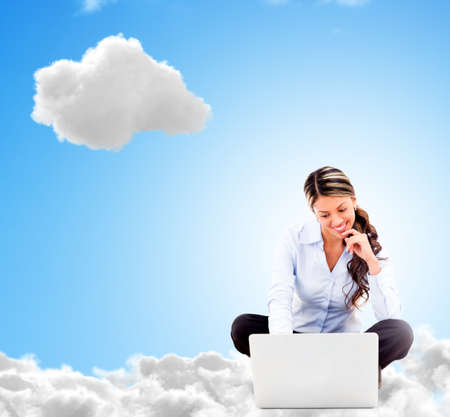 Business woman working online from a cloud and looking happy photo