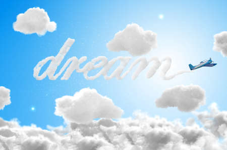 3D Airplane writing the word dream in the sky - travel concepts photo