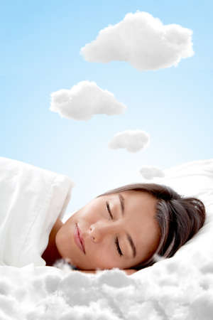 Peaceful woman sleeping on a cloud and having sweet dreams photo