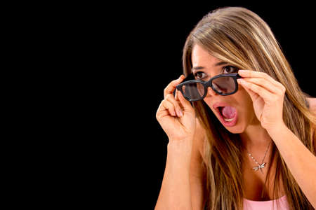 Shocked woman watching 3D movie - isolated over a black background photo