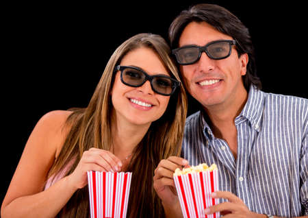 Happy couple watching a 3D movie and wearing glasses photo