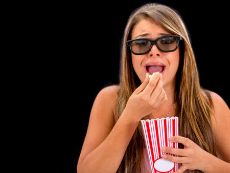 Scared woman watching a 3D movie - isolated over a black background photo