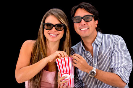 Couple watching movie in 3D - isolated over a black background photo