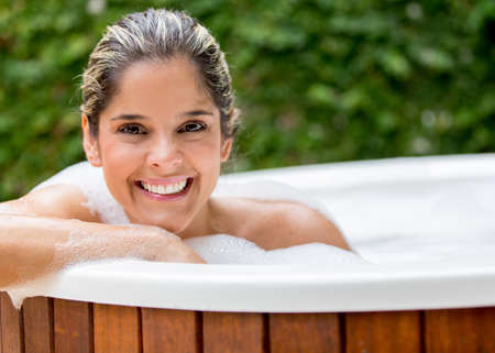 Happy woman taking a bath in the hot tub photo