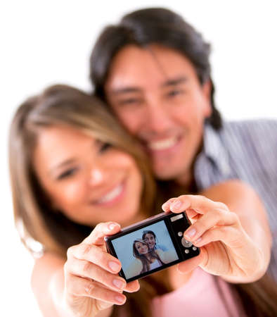 Happy couple taking a picture of themselves with a camera - isolated photo