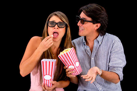Couple at the movies wearing 3D glasses - isolated over black background photo