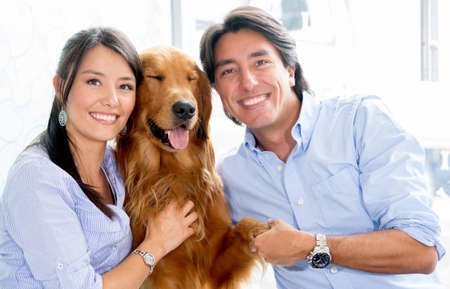 Happy couple holding their dog Stock Photo - 19056428