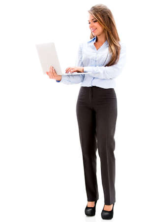 Business woman standing a holding a laptop. Isolated over white photo