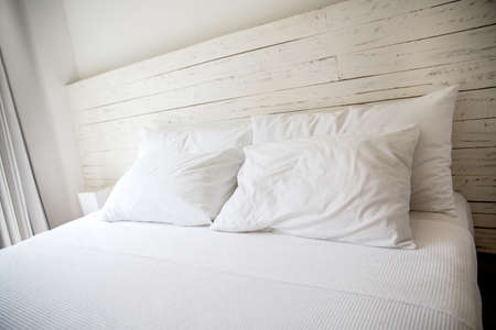 White bedroom with a king size bed and pillows. photo