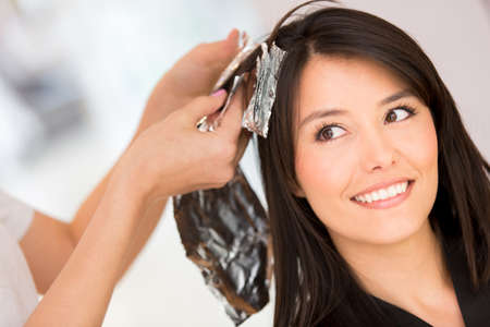 Brunette woman dying her hair at the beauty salon photo