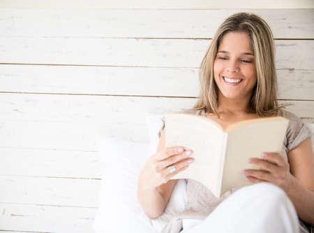 mujer leyendo libro: Mujer feliz descansando en su casa y leer un libro Foto de archivo